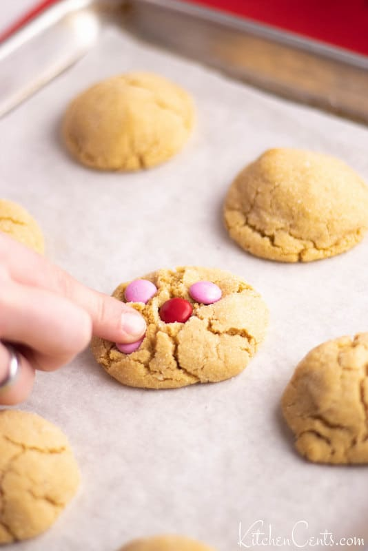 Placing M&Ms in par baked peanut butter cookies | Kitchen Cents